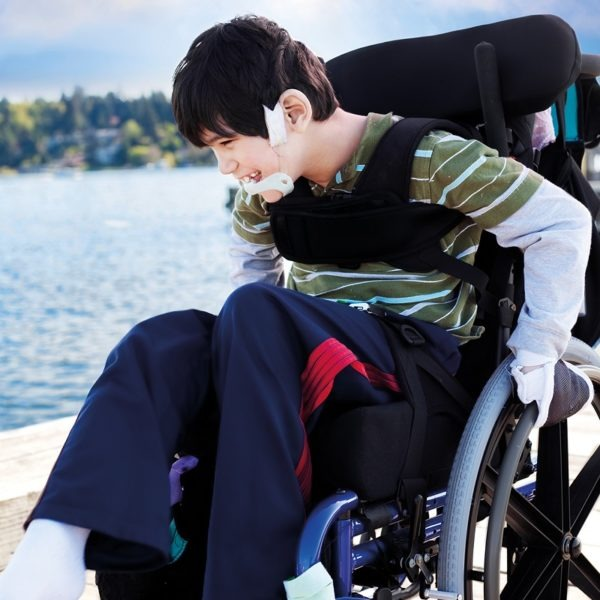Disabled little boy in wheelchair out on pier by lake - accessible holidays