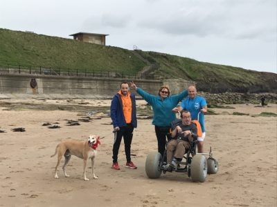 Group shot on beach, 3 people standing, 1 person using their Nomad and 1 dog!