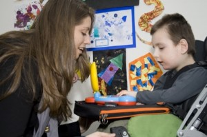 little boy in wheelchair using his trabasack curve connect as a sensory play tray with young young woman