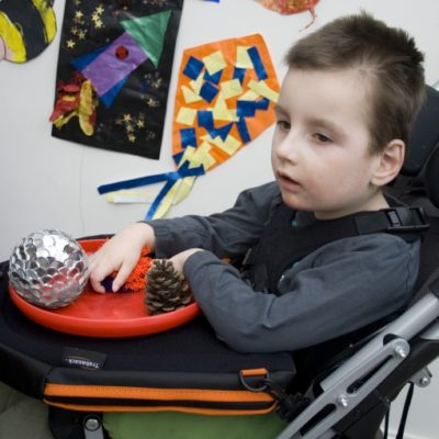 Little boy in wheelchair using a Trabasack curve connect as a sensory play tray
